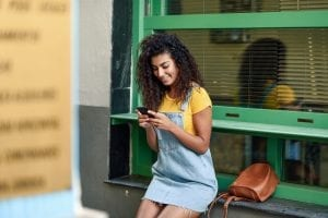 A young woman is looking at a mobile optimized website on mobile device