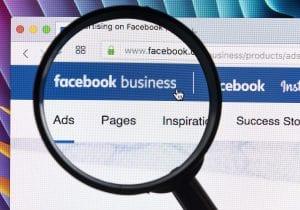 Magnifying glass enlarging Facebook Business logo