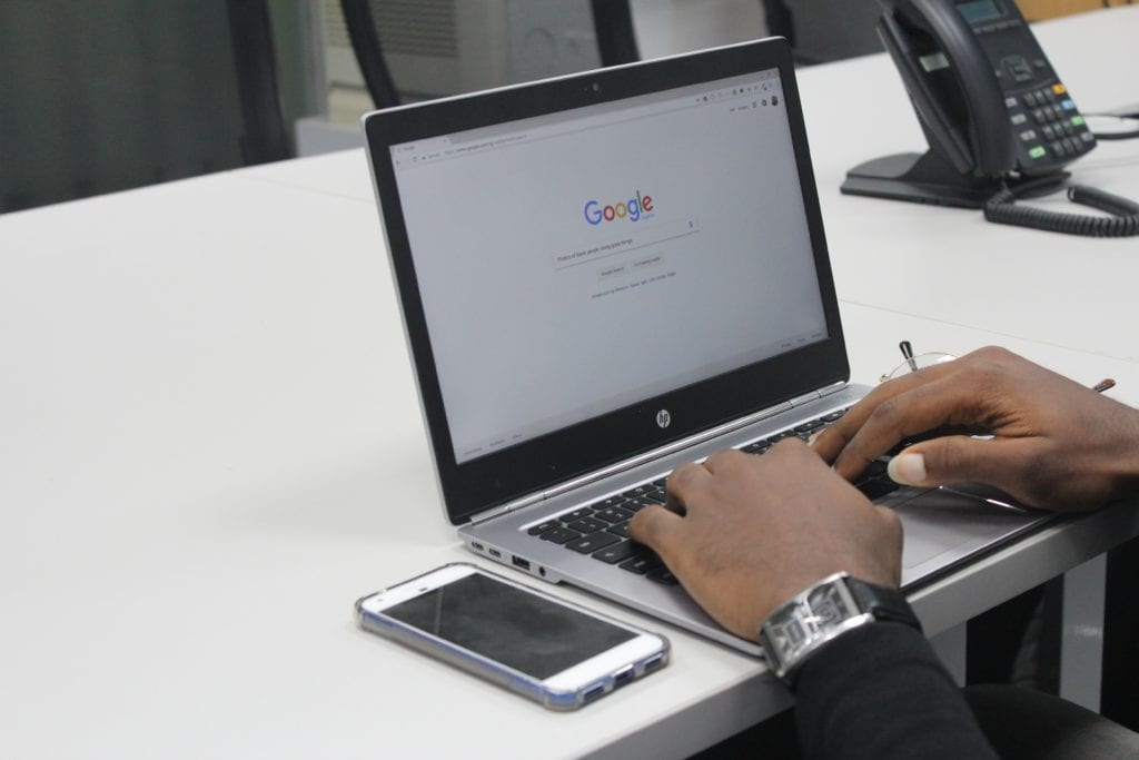 Man typing on laptop with Google Search open in browser
