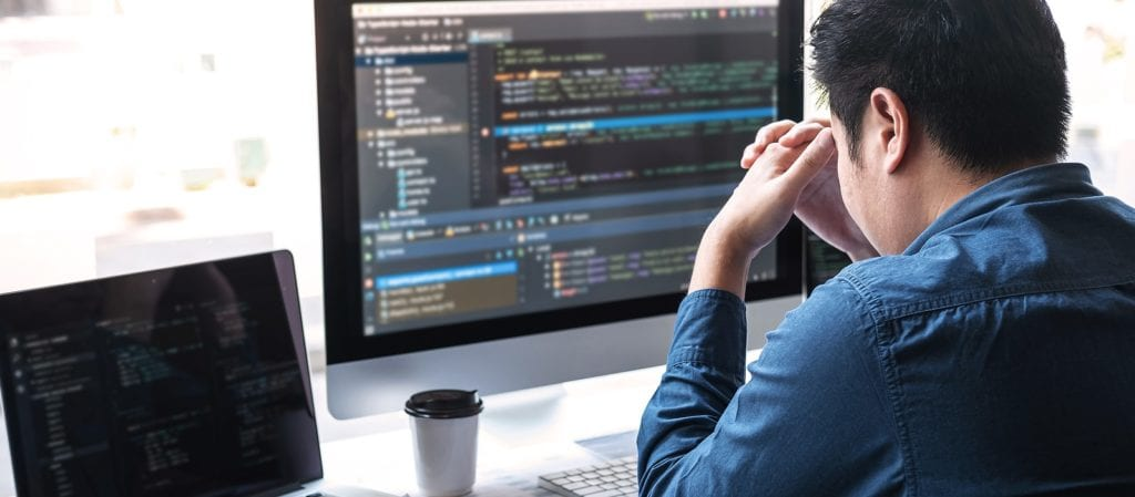 stressed man at computer editing source code on website