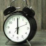 black alarm clock showing time to learn spanish